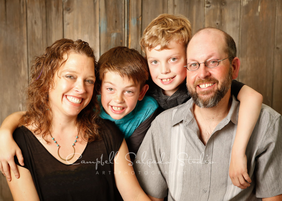 Portrait of family on barn doors background by family photographers at Campbell Salgado Studio in Portland, Oregon.