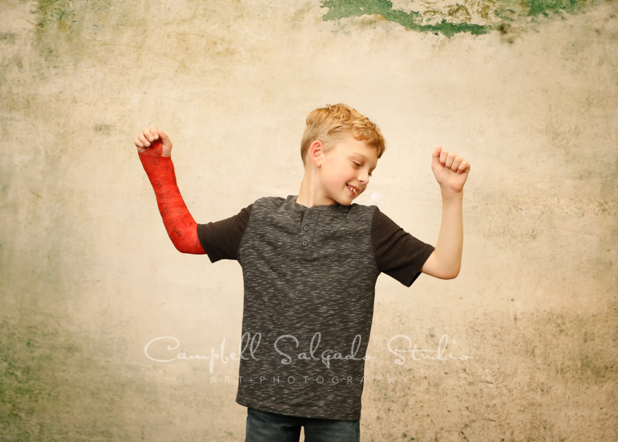 Portrait of child on weathered green background by child photographers at Campbell Salgado Studio in Portland, Oregon.