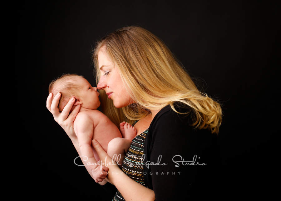 Portrait of mother and newborn on black background by newborn photographers at Campbell Salgado Studio in Portland, Oregon.