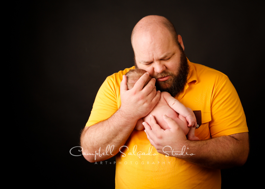 Portrait of father and newborn on black background by newborn photographers at Campbell Salgado Studio in Portland, Oregon.
