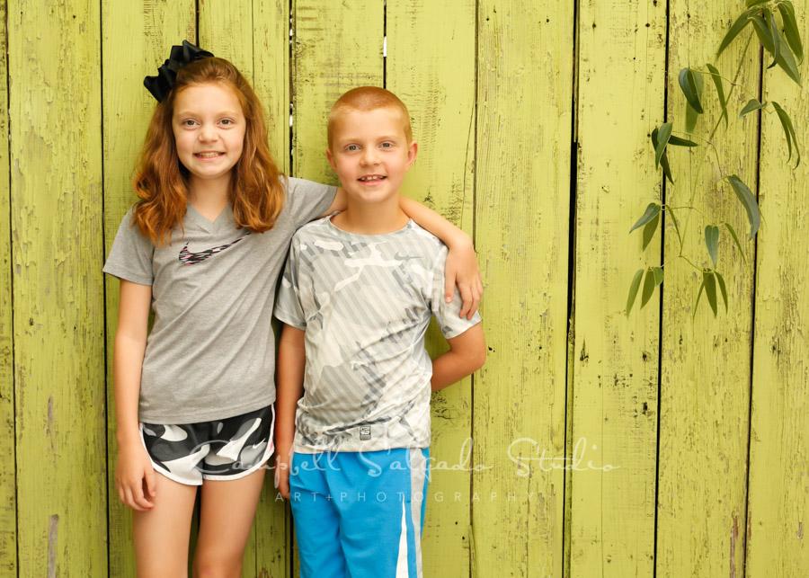 Portrait of kids on lime fenceboards background by children's photographers at Campbell Salgado Studio in Portland, Oregon.