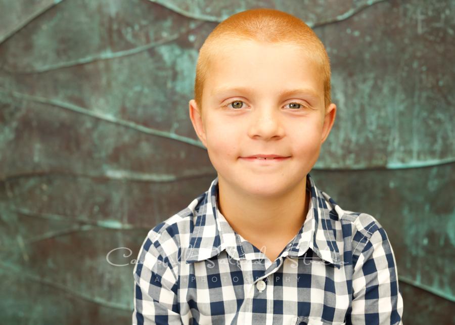 Portrait of boy on ocean weave background by child photographers at Campbell Salgado Studio in Portland, Oregon.