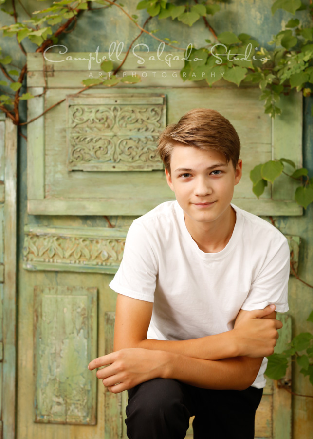 Portrait of teen on vintage green doors background by teen photographers at Campbell Salgado Studio in Portland, Oregon.