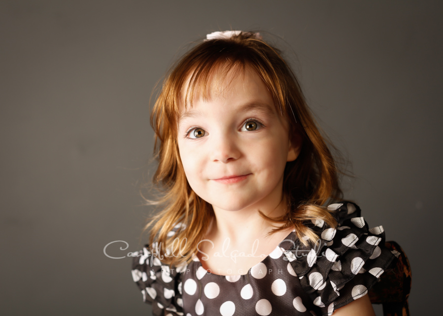 Portrait of girl on gray background by child photographers at Campbell Salgado Studio in Portland, Oregon.