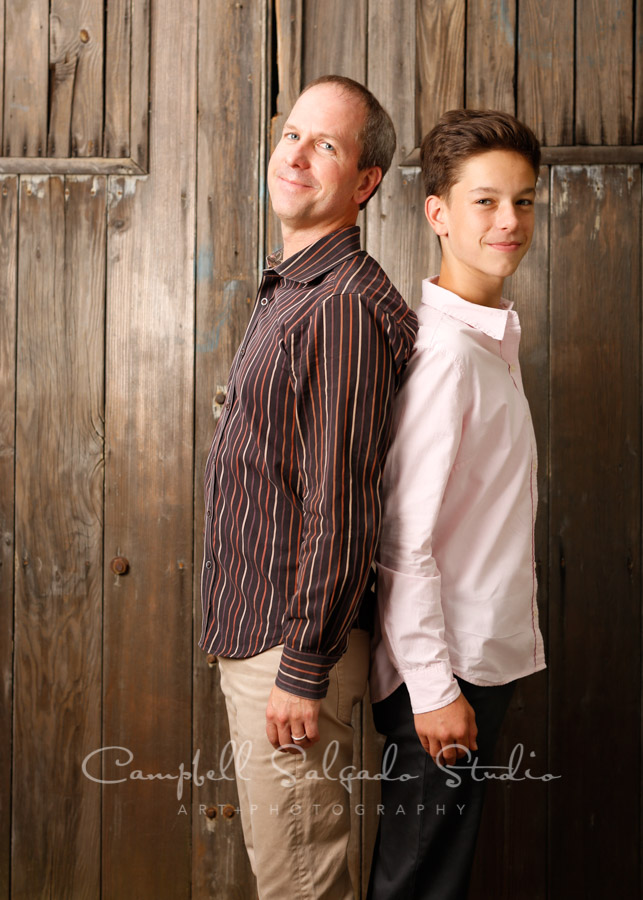 Portrait of father and son on barn doors background by family photographers at Campbell Salgado Studio in Portland, Oregon.