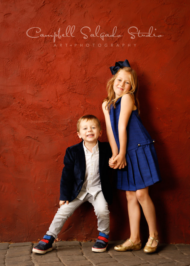 Portrait of children on red stucco background by childrens photographers at Campbell Salgado Studio in Portland, Oregon.