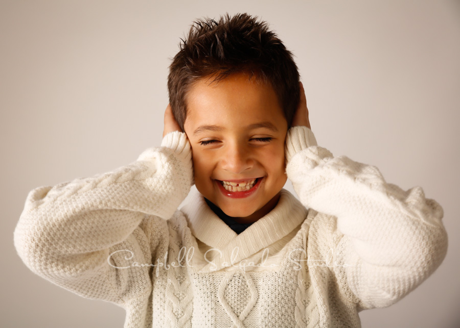 Portrait of boy on light grey background by childrens photographers at Campbell Salgado Studio in Portland, Oregon.