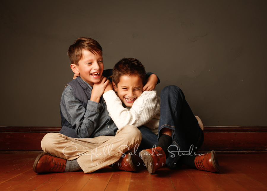 Portrait of boy twins on grey background by childrens photographers at Campbell Salgado Studio in Portland, Oregon.