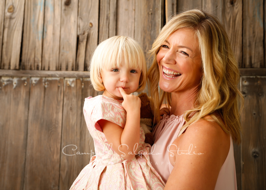 Portrait of mother and daughter on barn doors background by family photographers at Campbell Salgado Studio in Portland, Oregon.