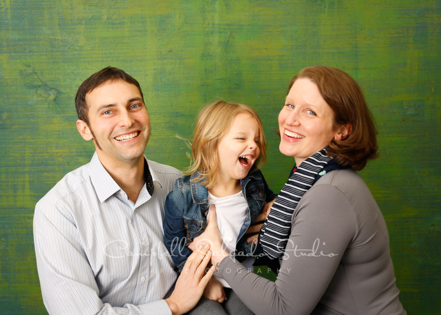 Portrait of family on blue-green weave background by family photographers at Campbell Salgado Studio in Portland, Oregon.