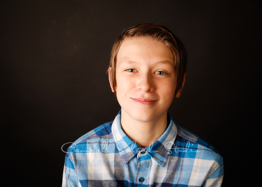 Portrait of boy on black background by child photographers at Campbell Salgado Studio in Portland, Oregon.