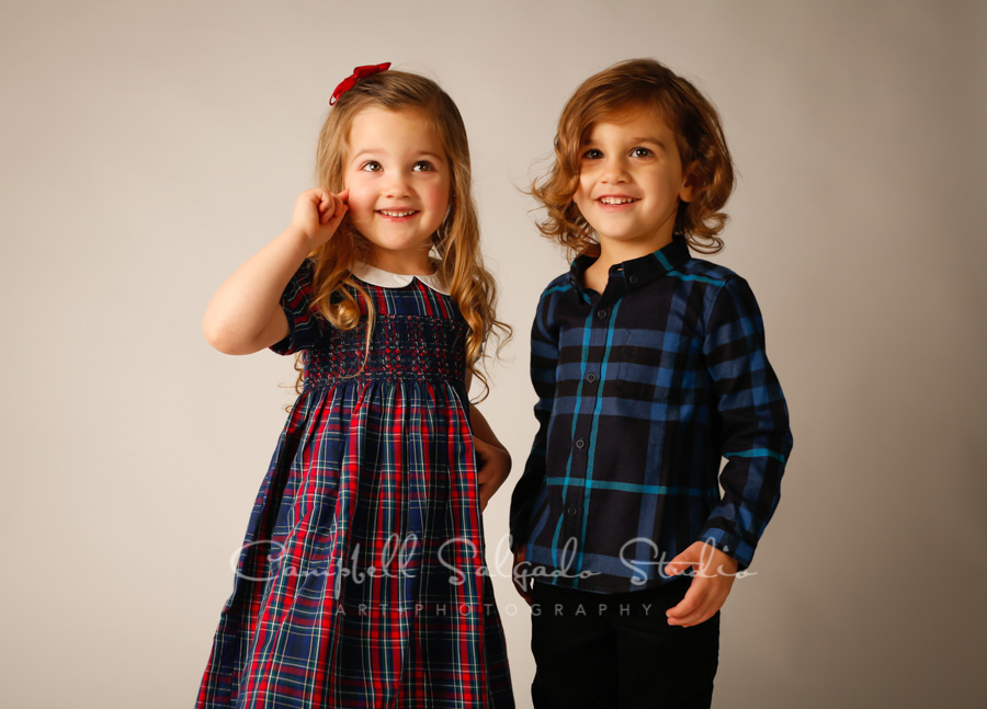 Portrait of twin toddlers on light grey background by child photographers at Campbell Salgado Studio in Portland, Oregon.