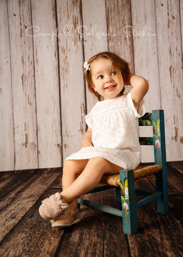 Portrait of toddler on white fenceboards background by child photographers at Campbell Salgado Studio in Portland, Oregon.
