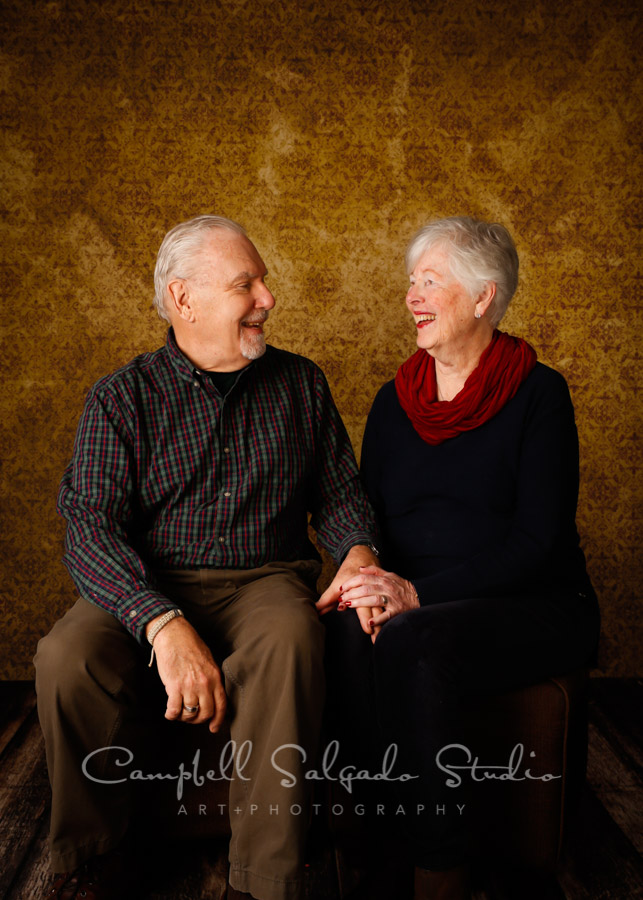 Portrait of couple on amber light background by couples photographers at Campbell Salgado Studio in Portland, Oregon.