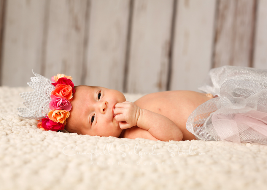 Portrait of newborn on white fenceboards background by newborn photographers at Campbell Salgado Studio in Portland, Oregon.