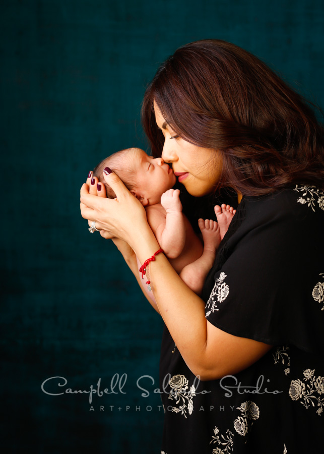 Portrait of mother and newborn on deep ocean background by newborn photographers at Campbell Salgado Studio in Portland, Oregon.