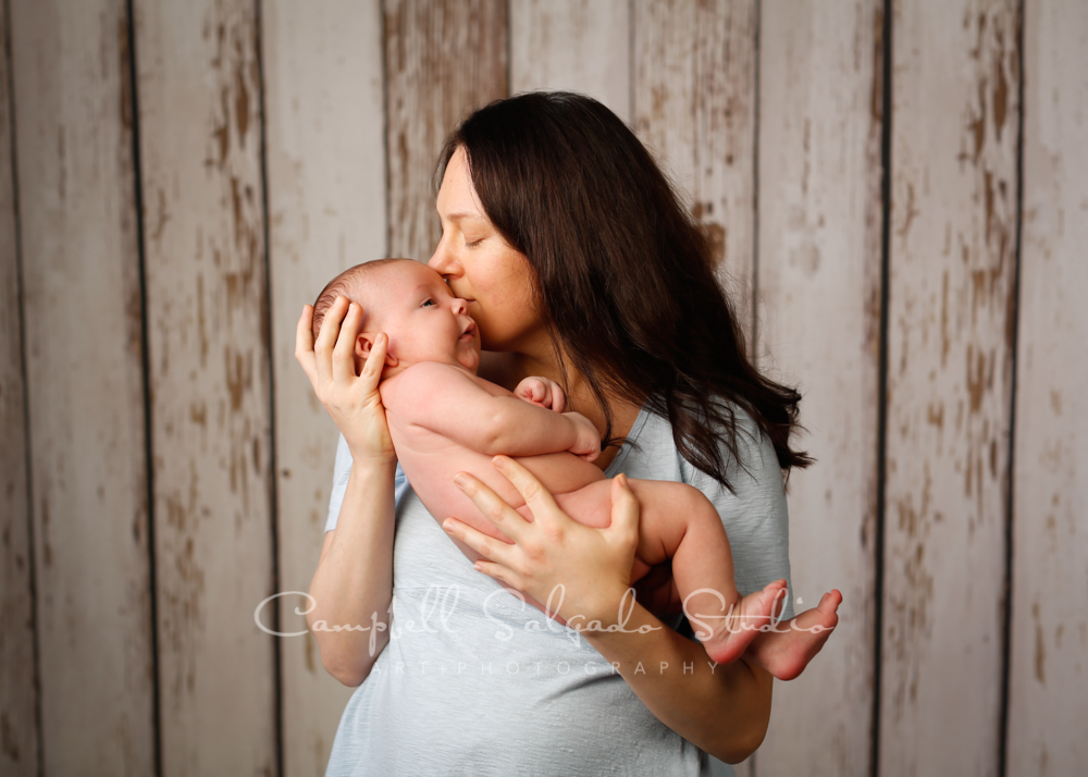 Portrait of mother and baby on white fenceboards background by newborn photographers at Campbell Salgado Studio in Portland, Oregon.