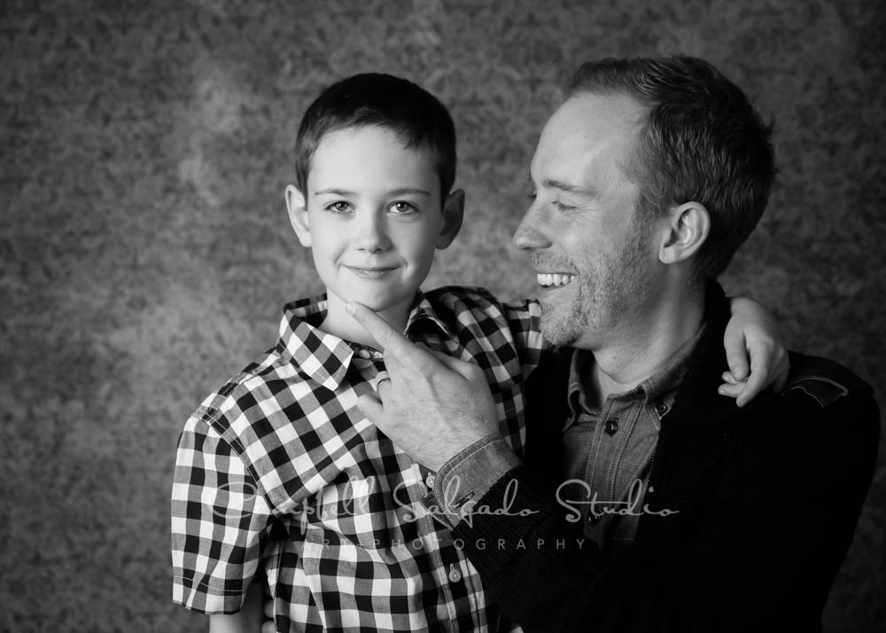 Black and white portrait of father and son on amber light background by family photographer at Campbell Salgado Studio in Portland, Oregon.