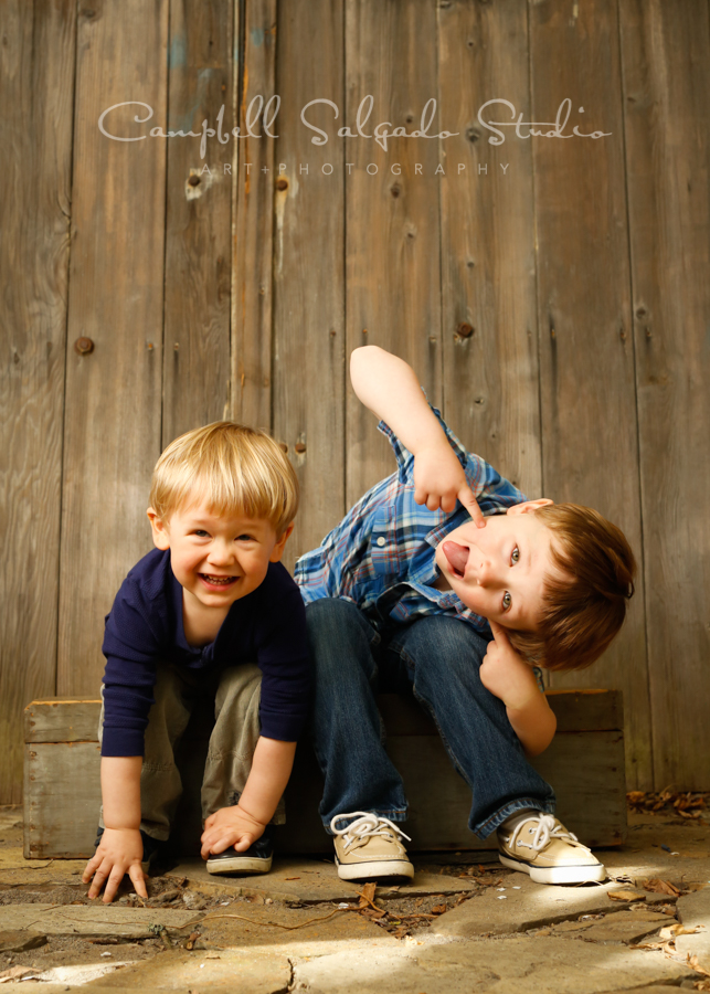 Portrait of children on barn doors background by children's photographers at Campbell Salgado Studio in Portland, Oregon.