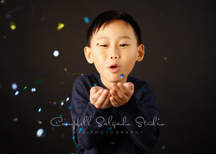 Portrait of boy on black background by child photographers at Campbell Salgado Studio in Portland, Oregon.