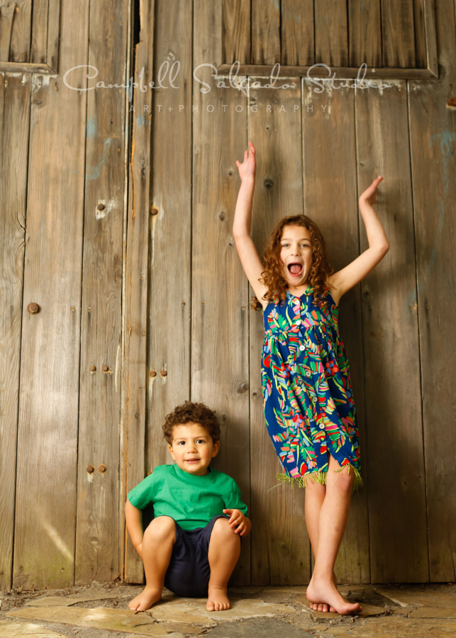 Portrait of children on barn doors background by child photographers at Campbell Salgado Studio in Portland, Oregon.