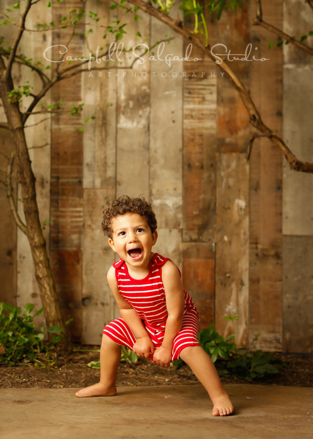 Portrait of child on wooden wall background by child photographers at Campbell Salgado Studio in Portland, Oregon.