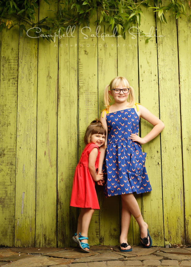 Portrait of girls on lime fenceboards background by children's photographers at Campbell Salgado Studio in Portland, Oregon.