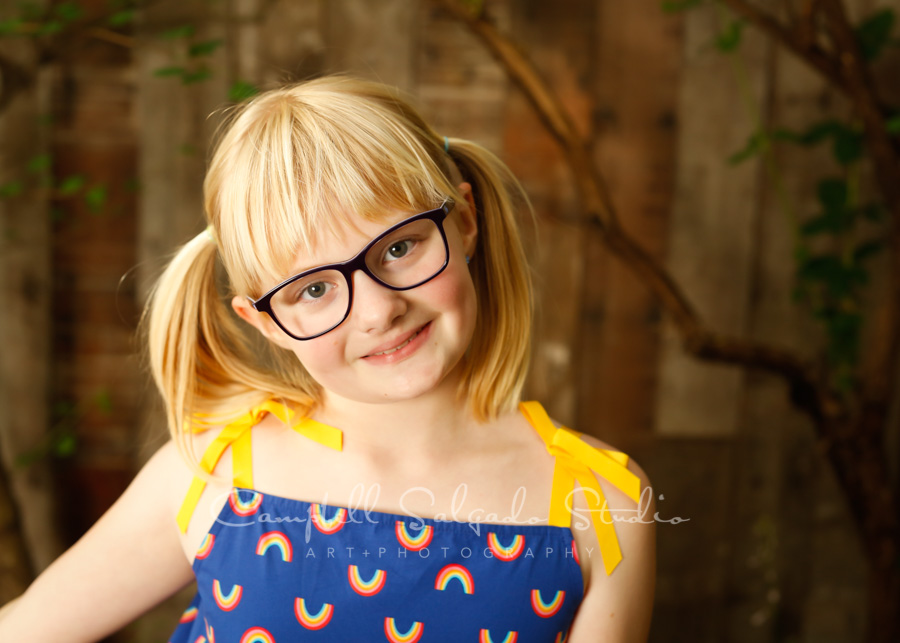 Portrait of girl on wooden wall background by child photographers at Campbell Salgado Studio in Portland, Oregon.