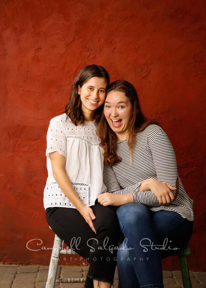 Portrait of girls on red stucco background by teen photographers at Campbell Salgado Studio in Portland, Oregon.