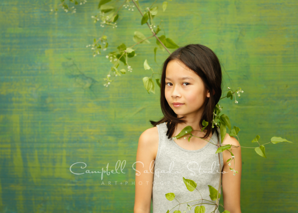 Portrait of girl on blue green weave background by child photographers at Campbell Salgado Studio in Portland, Oregon.