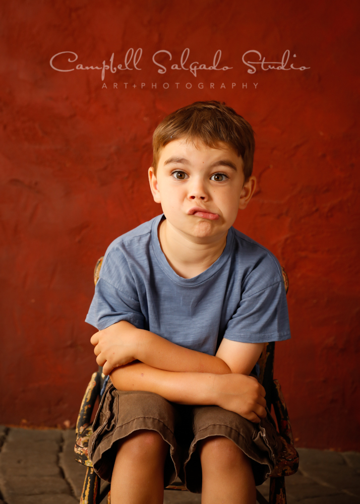 Portrait of child on red stucco background by children's photographers at Campbell Salgado Studio in Portland, Oregon.