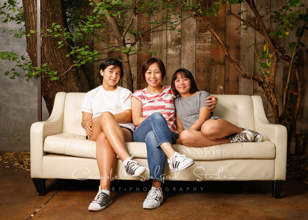 Portrait of family on wooden wall background by family photographers at Campbell Salgado Studio in Portland, Oregon.