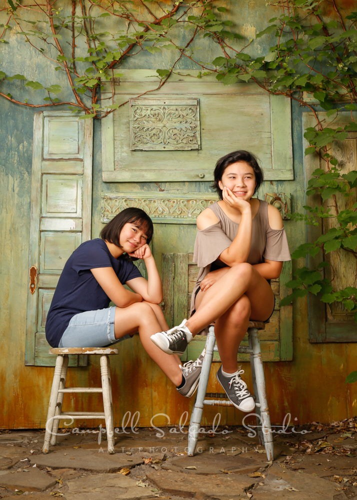 Portrait of girls on vintage green doors background by family photographers at Campbell Salgado Studio in Portland, Oregon.