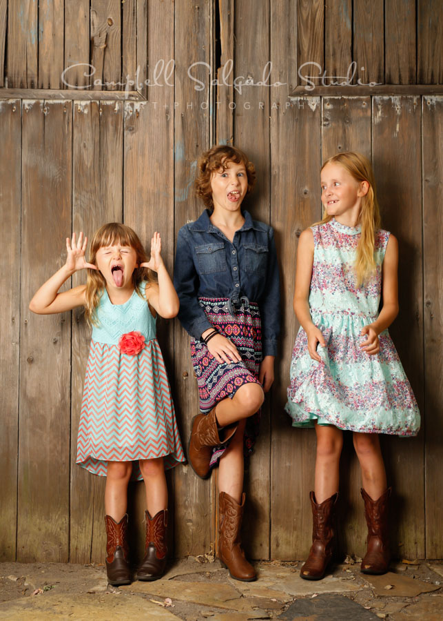 Portrait of kids on barn doors background by child photographers at Campbell Salgado Studio in Portland, Oregon.