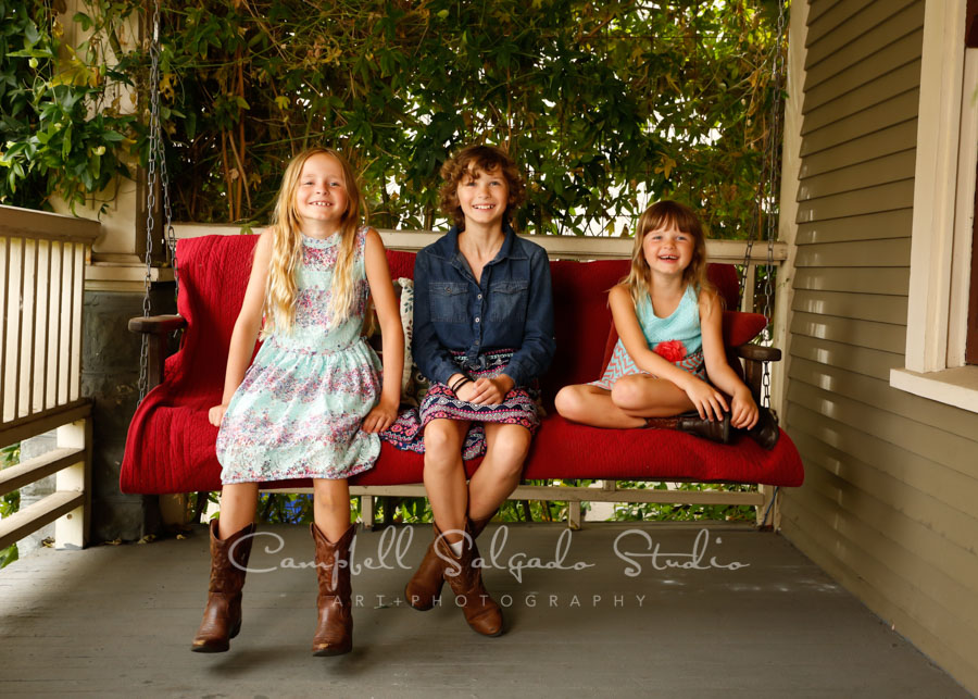 Portrait of kids on porch swing background by child photographers at Campbell Salgado Studio in Portland, Oregon.