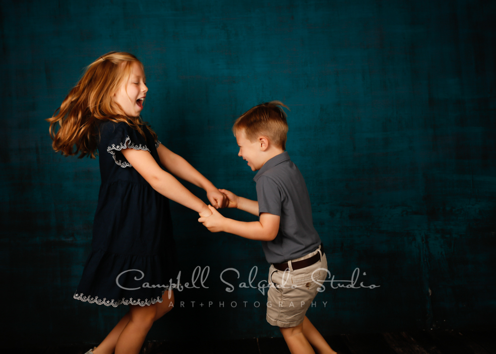 Portrait of kids on deep ocean background by children's photographers at Campbell Salgado Studio in Portland, Oregon.