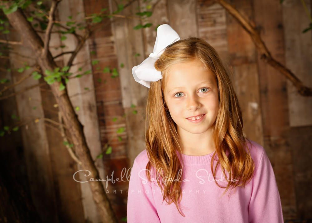 Portrait of girl on wooden wall background by  children's photographers at Campbell Salgado Studio in Portland, Oregon.