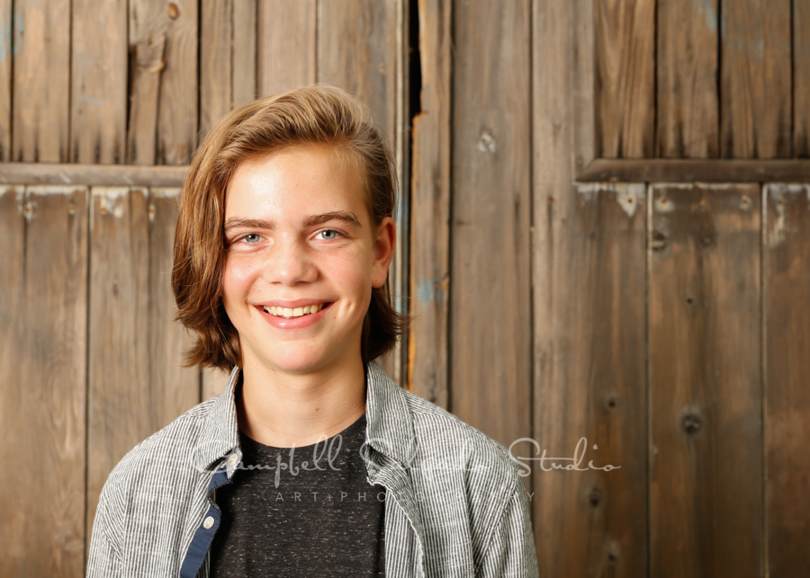 Portrait of teen on barn doors background by family photographers at Campbell Salgado Studio in Portland, Oregon.