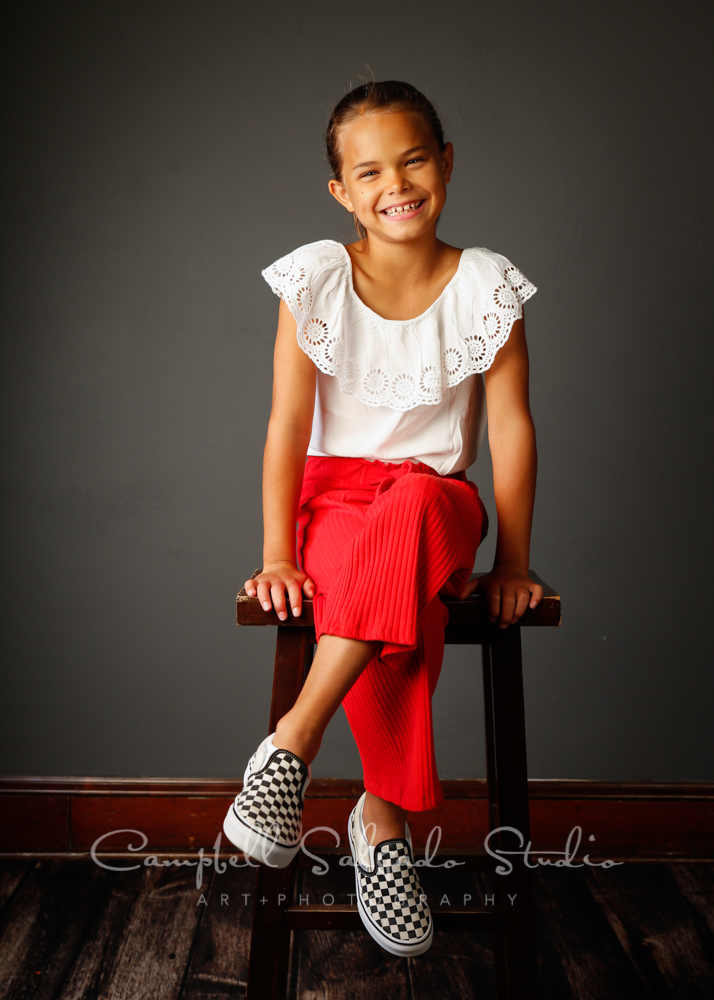 Portrait of child on gray background by child photographers at Campbell Salgado Studio in Portland, Oregon.