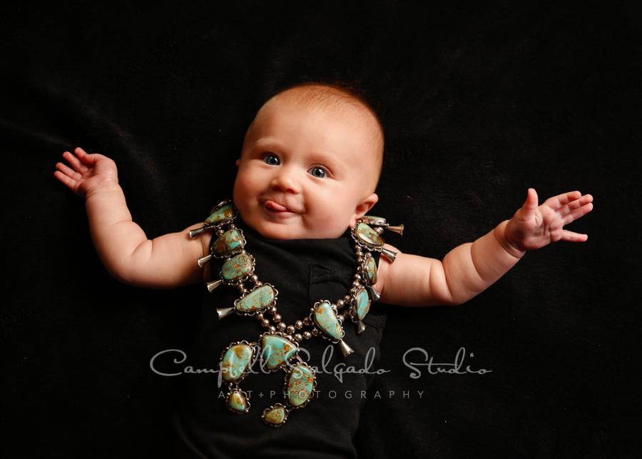 Portrait of infant on black background by infant photographers at Campbell Salgado Studio in Portland, Oregon.
