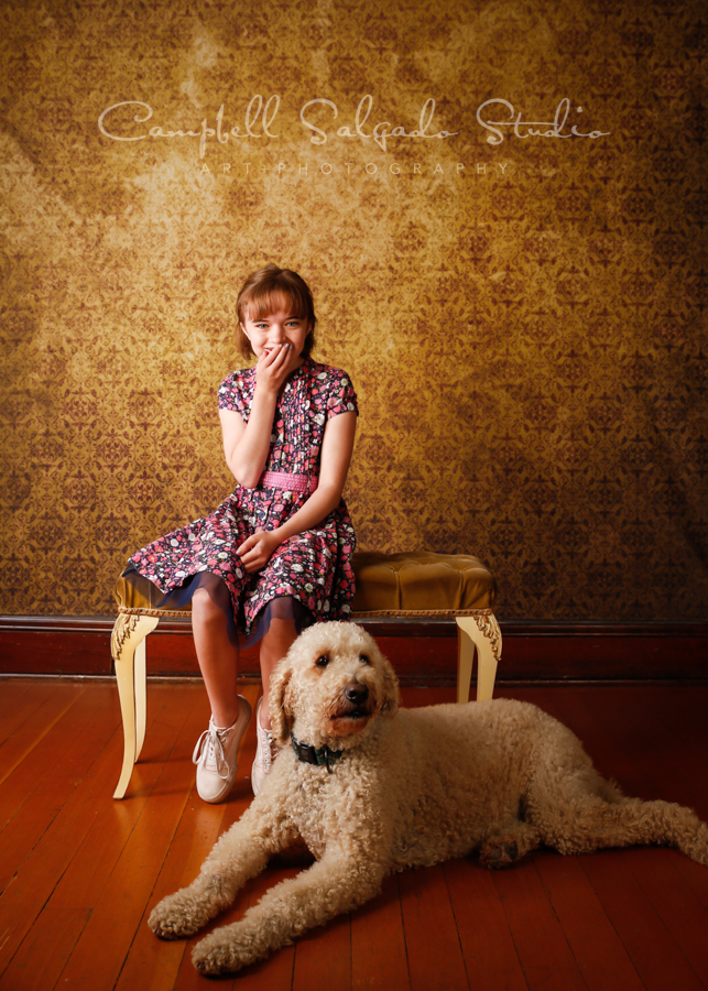 Portrait of girl and dog on amber light background by pet photographers at Campbell Salgado Studio in Portland, Oregon.