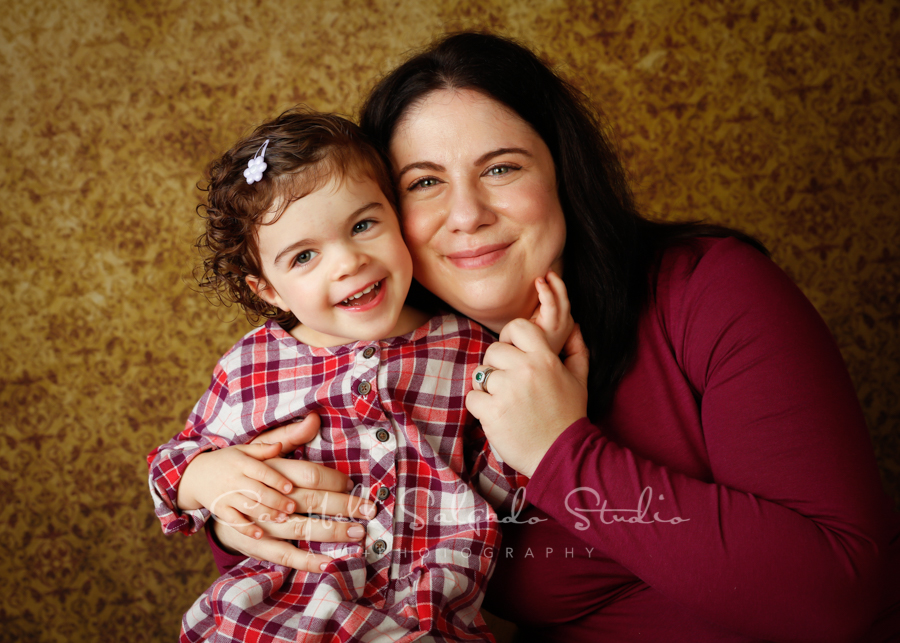 Portrait of mother and daughter on amber light background by family photographers at Campbell Salgado Studio in Portland, Oregon.