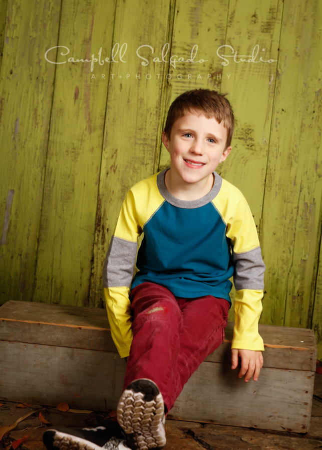 Portrait of boy on lime fenceboards background by child photographers at Campbell Salgado Studio in Portland, Oregon.