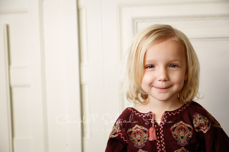 Portrait of child on white wooden doors background by child photographers at Campbell Salgado Studio in Portland, Oregon.
