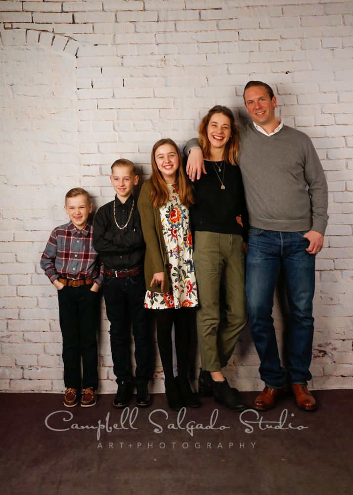 Portrait of family on white brick wall background by family photographers at Campbell Salgado Studio in Portland, Oregon.