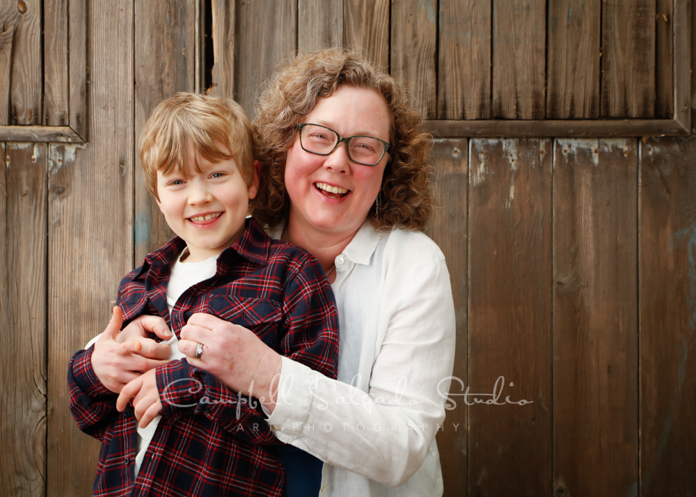 Portrait of mother and son on barn door background by family photographers at Campbell Salgado Studio in Portland, Oregon.