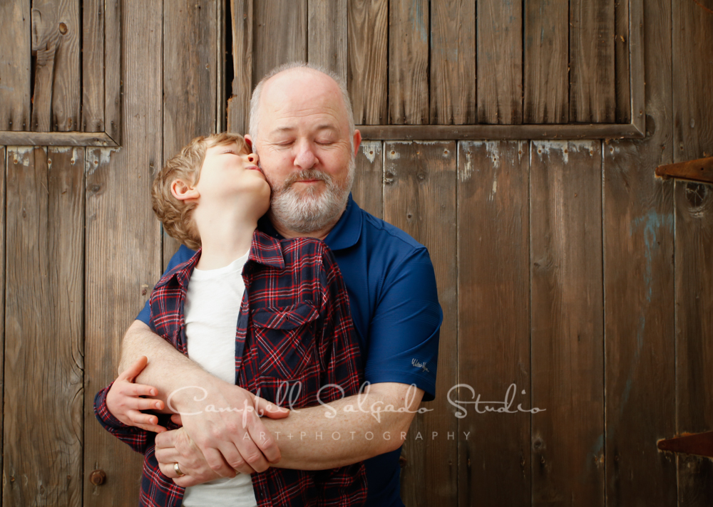 Portrait of father and son on barn door background by family photographers at Campbell Salgado Studio in Portland, Oregon.