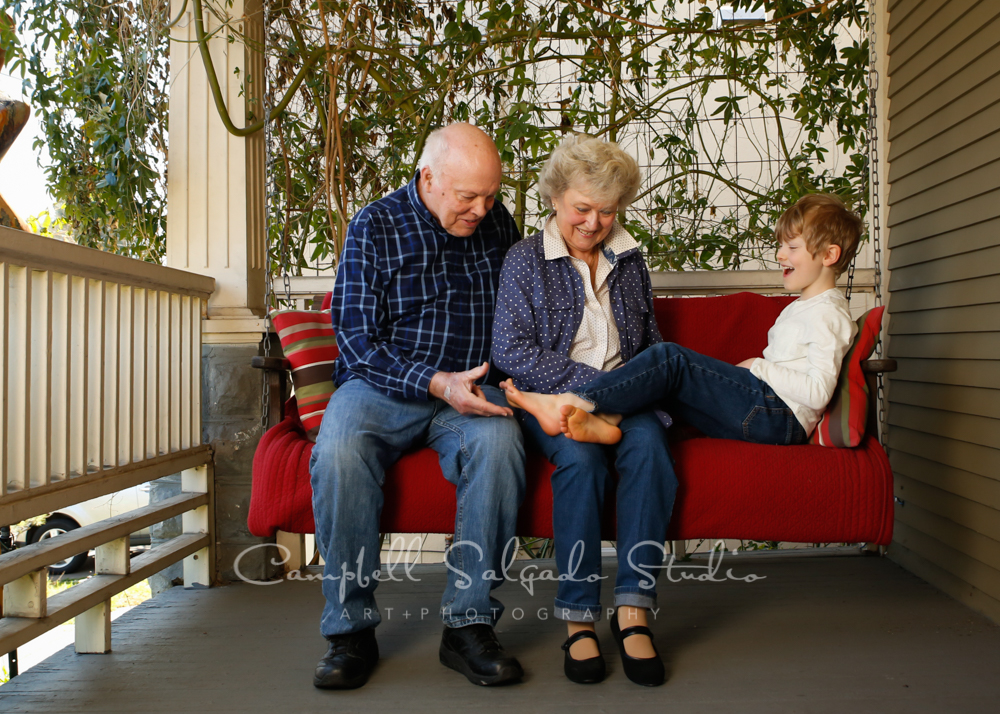 Portrait of multi generational family on porch swing background by family photographers at Campbell Salgado Studio in Portland, Oregon.