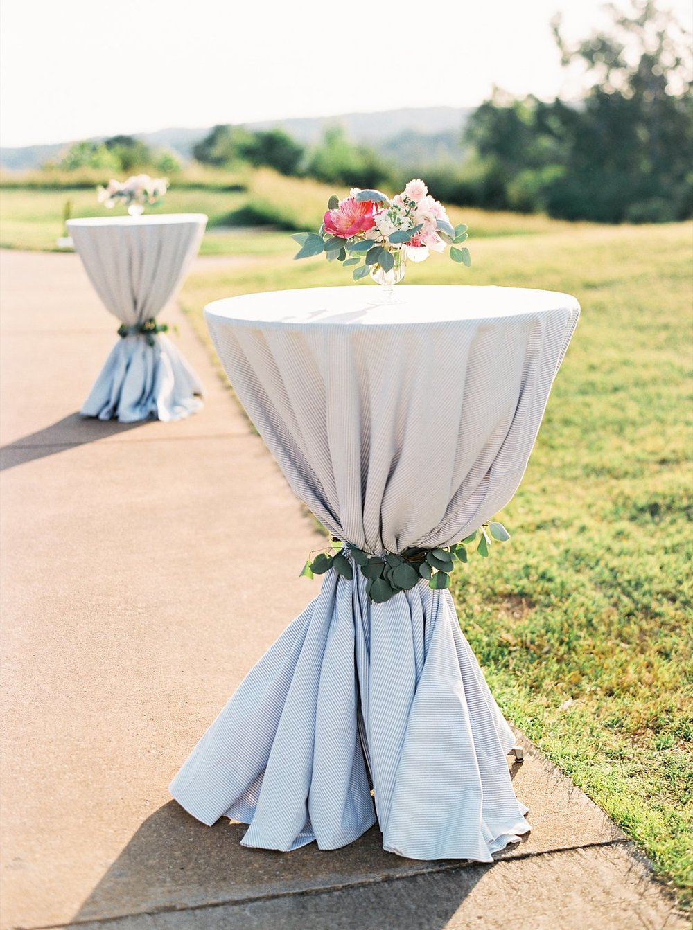 Cocktail Hour French Blue Striped Cocktail Tables tied with Eucalyptus Leaves | Blush and Navy Wedding with Fuchsia, French Blue and Gold Accents | Simply Jessica Marie's Southern Wedding at Gettysvue Golf Course and Country Club in Knoxville Tennessee | Photo by Perry Vaile Photography