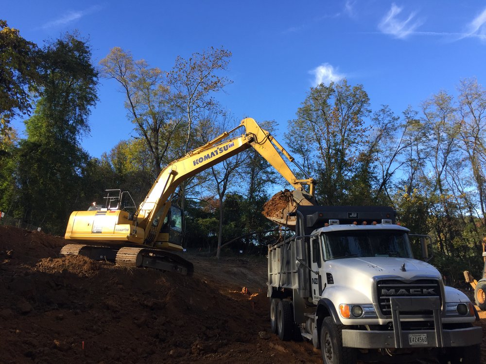 Excavator removes dirt from the hillside to level the dog park.